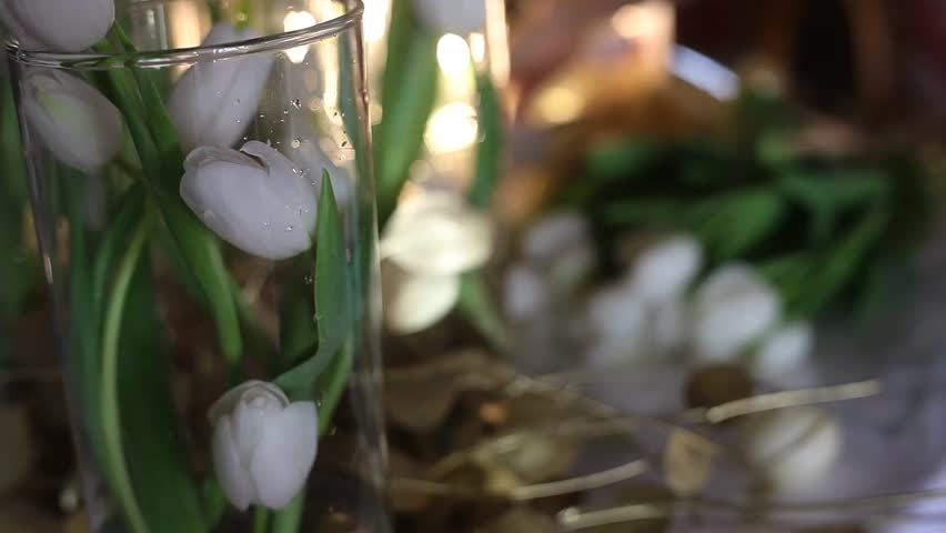 Florist at work. White Tulips in Clear Glass Vases, Golden Flowers on the Table #24324656
