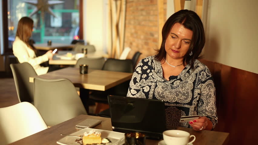 Woman with laptop doing online shopping in the cafe     Shutterstock HD Video #24358262