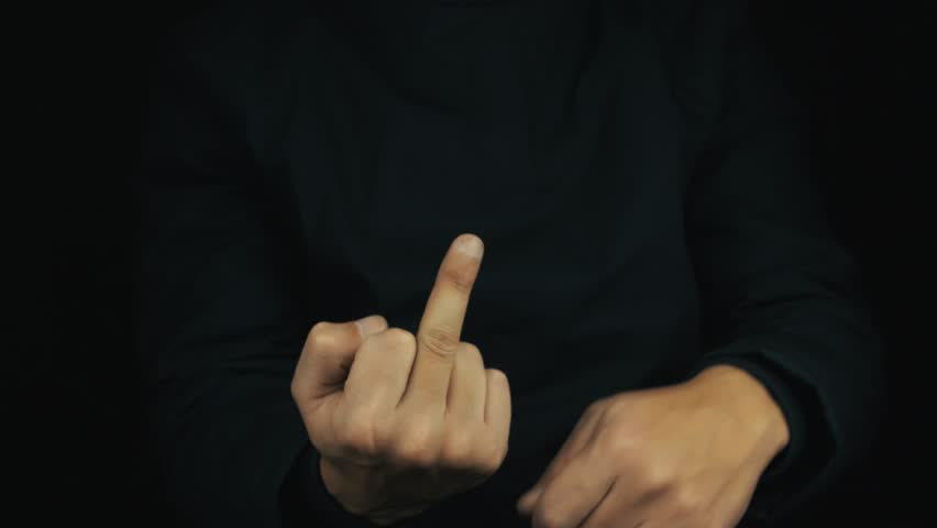 Caucasian male hand in long sleeve jacket mimic jack-in-the-box making obscene middle finger sign gesture on black background, close up isolated