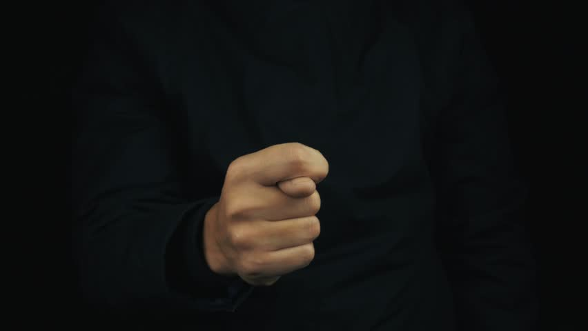 Caucasian male hand in long sleeve jacket making obscene sign gesture on black background, close up isolated