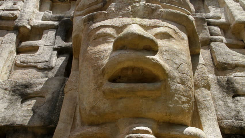 """Pan of a face on a Mayan Temple in Lamanai (""""submerged crocodile"""") in Belize"""