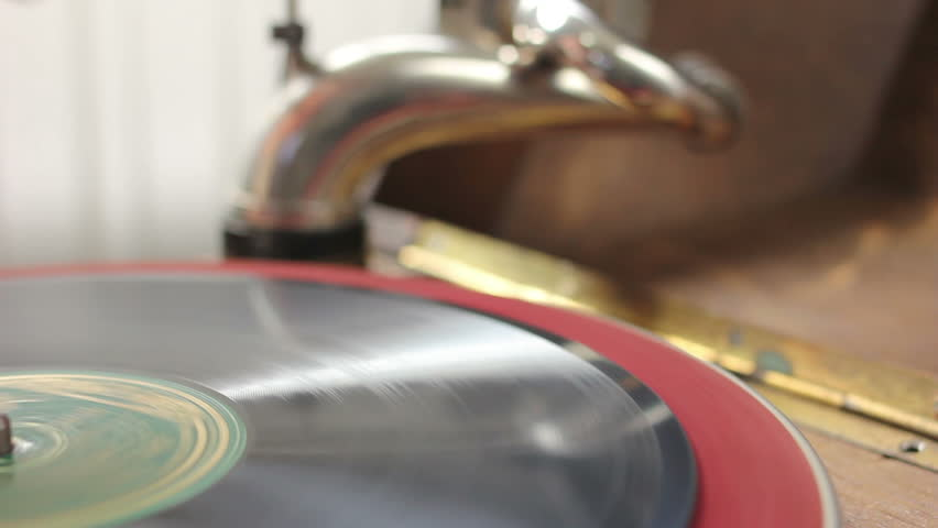 Hand putting vintage gramophone in starting position