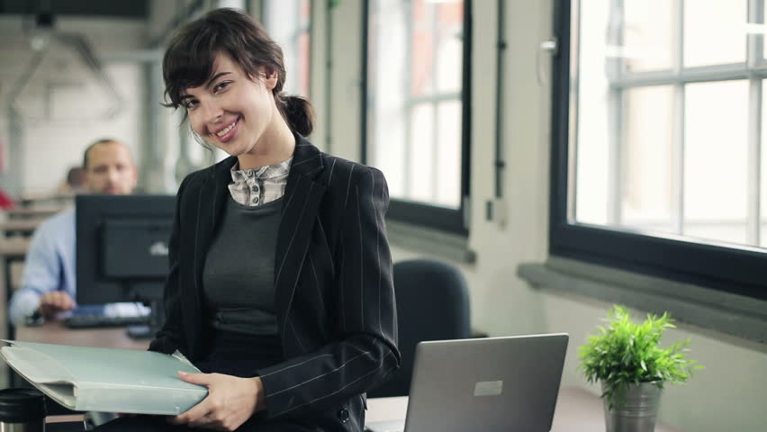 Portrait of happy businesswoman with documents in the office  - HD stock footage clip