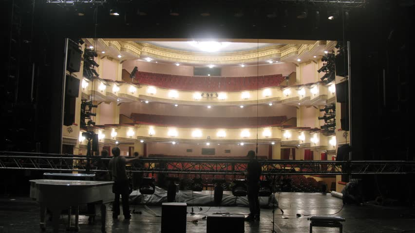 Working scenes dismantle scenery after performance against an empty spectator hall in theatre, time lapse