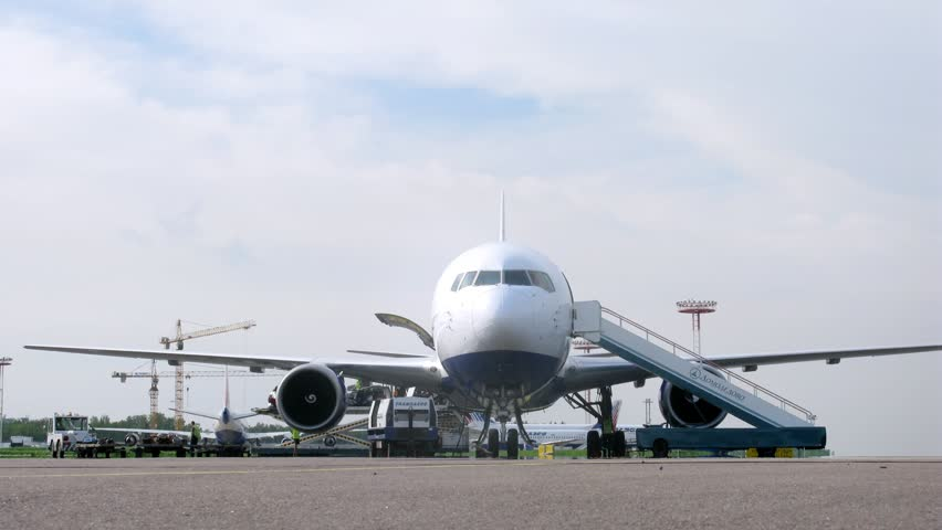 MOSCOW - MAY 22: (Timelapse View) Workers unload plane against cranes, on Domodedovo airport, on May 22, 2012 in Moscow, Russia