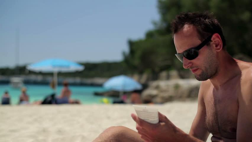 Man applying sun block lotion on the beach, dolly shot - HD stock video clip