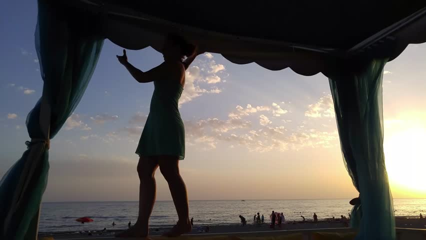 Silhouette of woman walking on border under tent in sunset on beach, mobile phone video. | Shutterstock HD Video #24705680