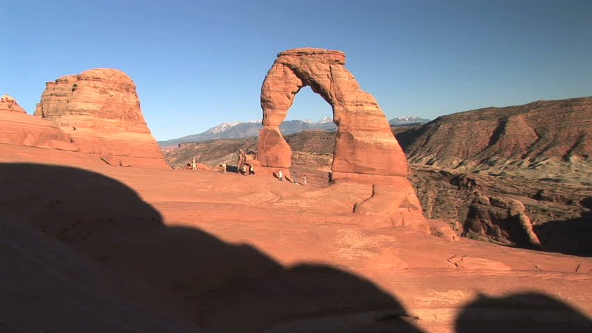 Nondescript tourists walking by Delicate Arch, Arches National Park, time lapse