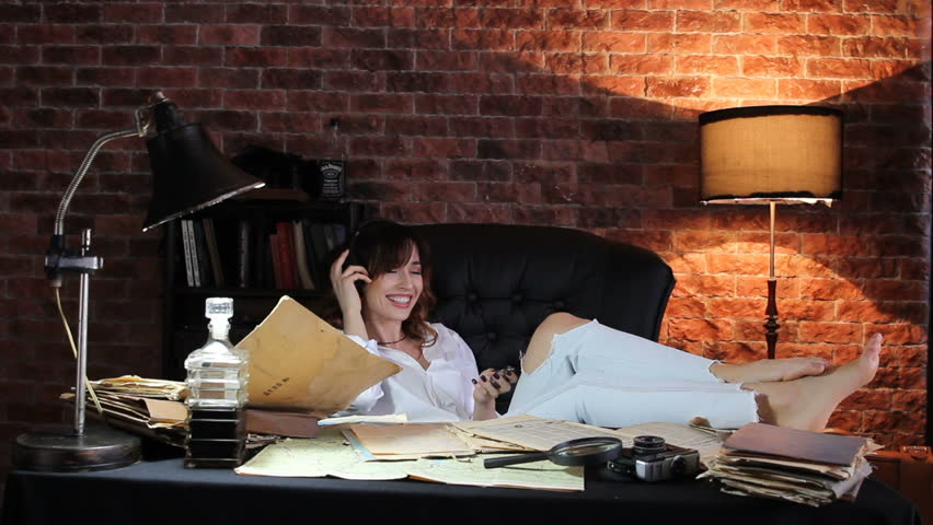 Pretty brunette woman in ripped jeans and white short sitting in armchair with legs on the table and listen music at headphones | Shutterstock HD Video #25063115