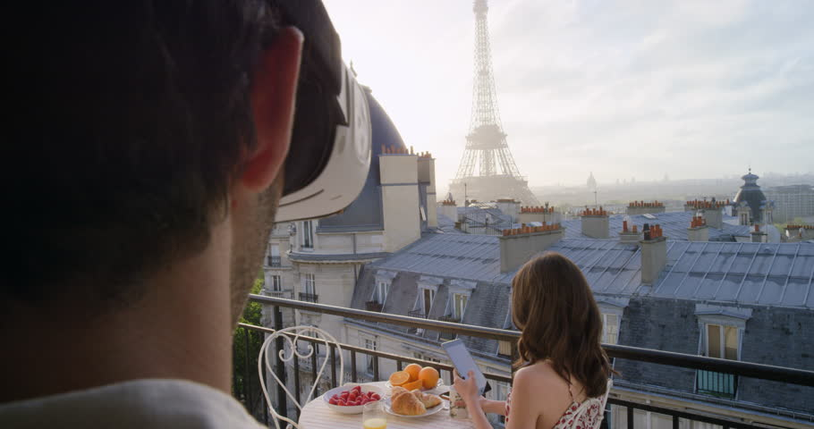Young man wearing virtual reality headset watching dream girl on Paris Hotel balcony view of Eiffel Tower 360 video imagination concept | Shutterstock HD Video #25126250