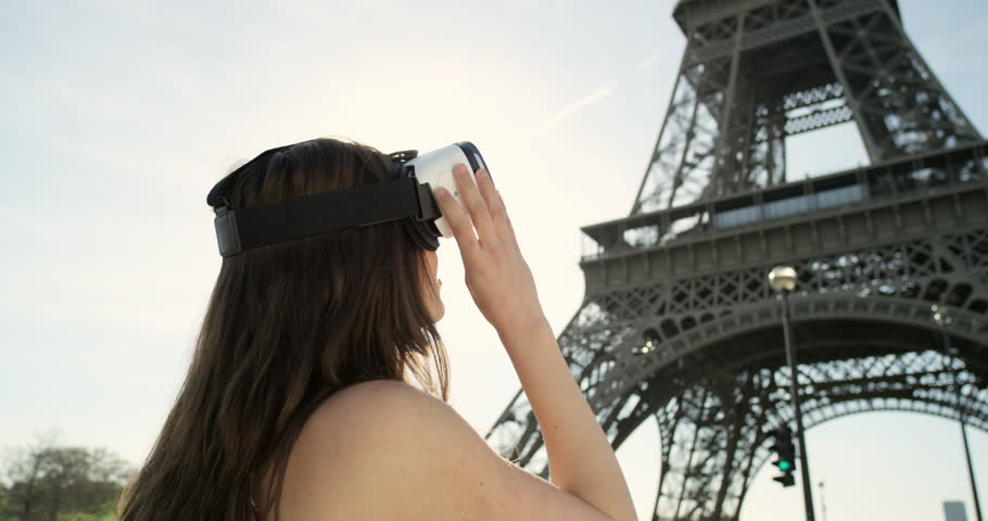 Young tourist woman at Eiffel tower Paris wearing virtual reality headset watching 360 video imagination VR concept   Shutterstock HD Video #25126880