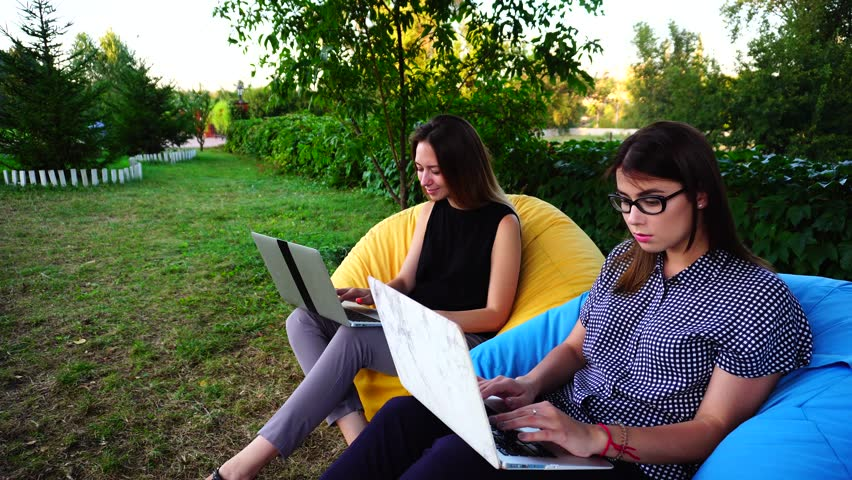 Educated Women Specialists Engaged in Preparing Accounts For Computer and Providing Them to Tax Authorities and State Funds, Sitting in Comfortable Colored Armchairs in Open Air on Warm Summer Day. | Shutterstock HD Video #25129256