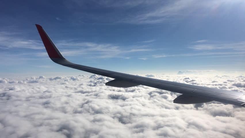Traveling by air. View through an airplane window.View of clouds through airplane window. | Shutterstock HD Video #25177595