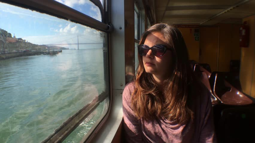 Young Woman In Lisbon Ferry. The ferry services of Lisbon that cross the Tejo River are an integral component of the capital's public transport network.   Shutterstock HD Video #25181501