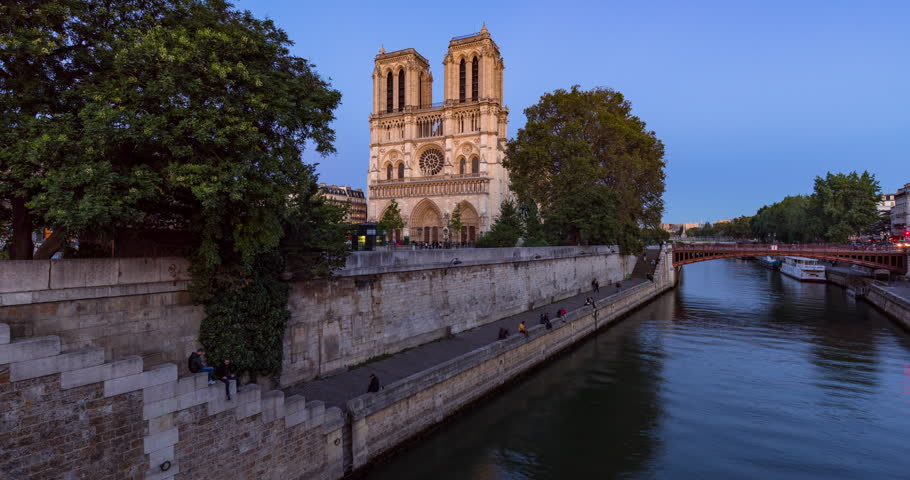 Notre Dame de Paris Cathedral and the Seine River at twilight. Time lapse of a summer evening with city lights in the 4th Arrondissement of Paris. France   Shutterstock HD Video #25184102