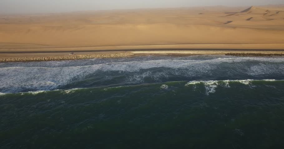 Drone video of view of Namibian Atlantic coastline, Swakopmund town buildings, beach, old pier, surf break point and landscape of ocean background of Swakopmund holiday resort at Namibia's west coast | Shutterstock HD Video #25185830