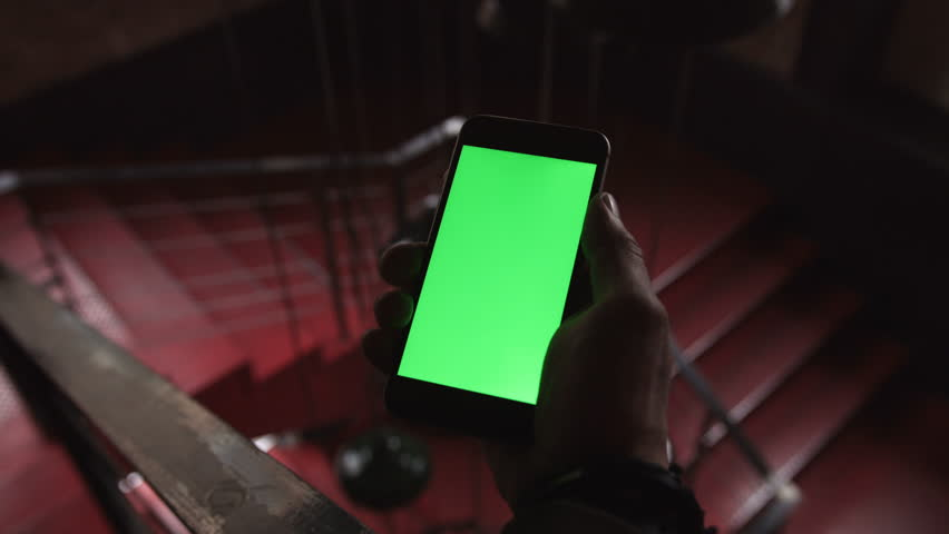 Close-up of a man holding and touching the phone with green screen in the background red stairs | Shutterstock HD Video #25230452