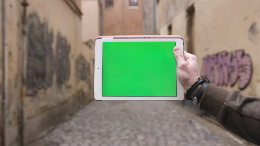 Closeup hand of man holding tablet computer with horizontal green screen on the streets | Shutterstock HD Video #25230461