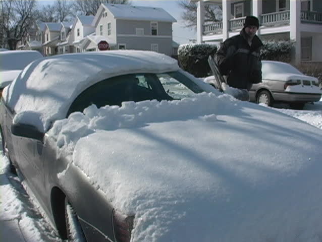 Man cleaning off his car after a lot of snow. - SD stock video clip