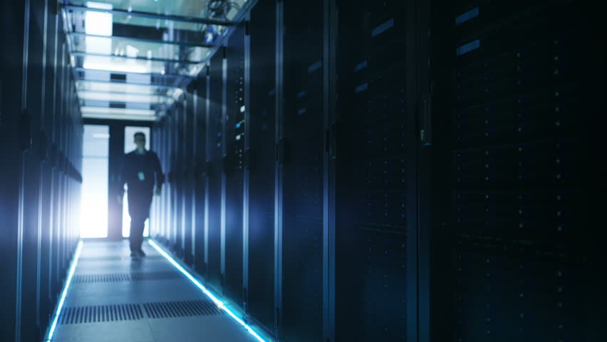 IT Engineer Holding Notebook and Walking Through Data Center Full of Working Rack Servers. Shot on RED EPIC-W 8K Helium Cinema Camera.
