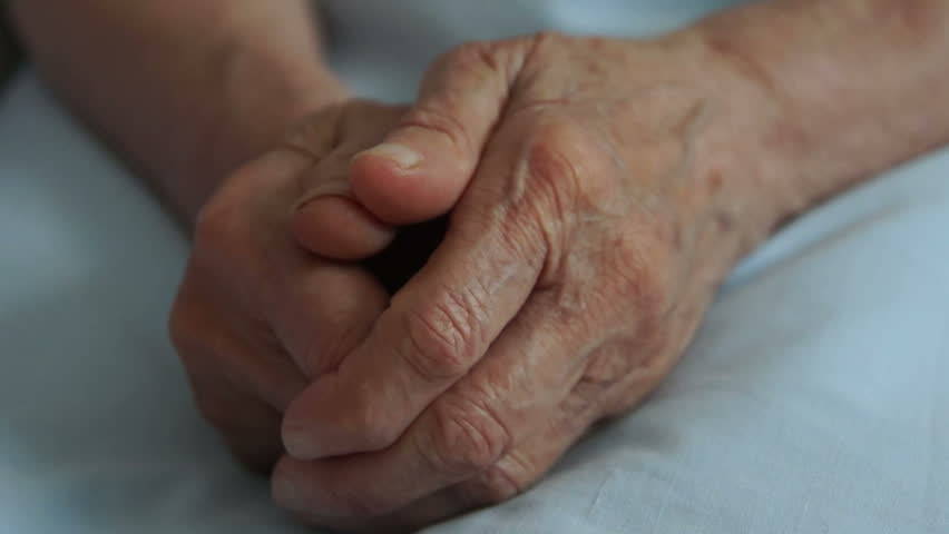 A young hand comforting an elderly pair of hands.
