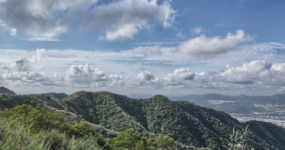 4K HDR Time-lapse of Burbank - from mountaintop overlooking Burbank with the Los Angeles skyline in the distance. Blue sky with billowing white clouds and green Verdugo mountains overlooking Burbank.  | Shutterstock HD Video #25340621