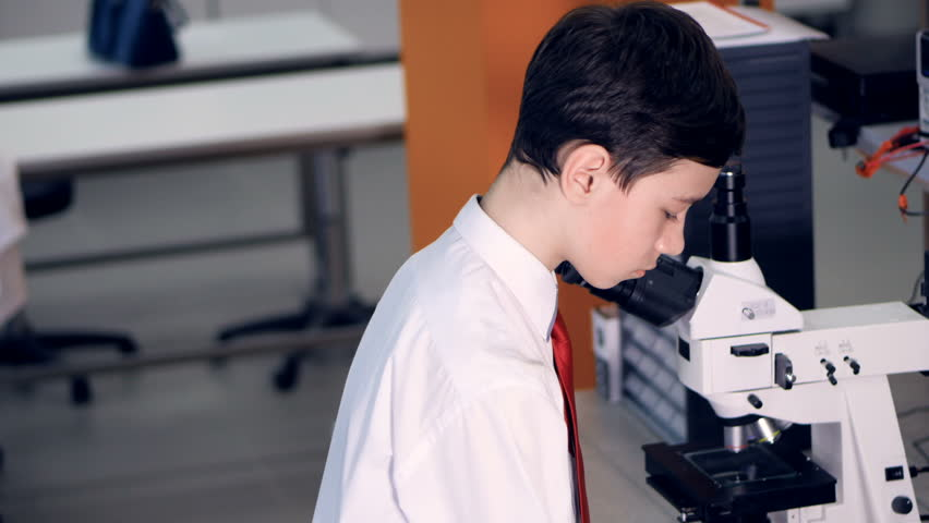 Teen at school laboratory studying biology, looking through microscope. | Shutterstock HD Video #25344383