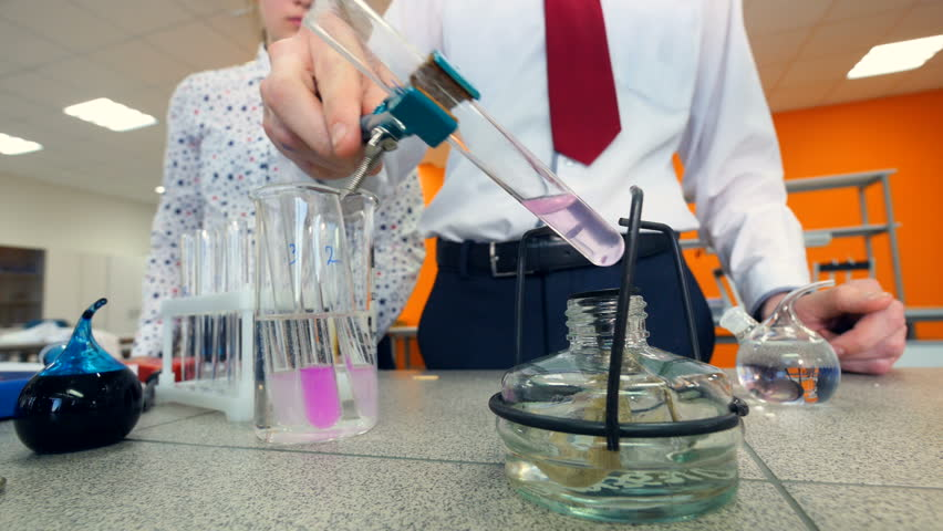 Elementary school students heating a test tube doing chemistry experiment in a science classroom. | Shutterstock HD Video #25344419