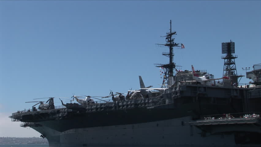 San Diego, CA - CIRCA June, 2008: View of different types of Navy aircraft on deck of the aircraft carrier docked in the bay on a sunny day - HD stock footage clip