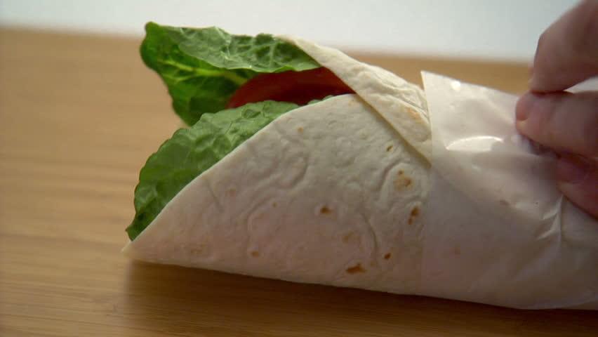 close-up preparation of chicken wrap sandwich