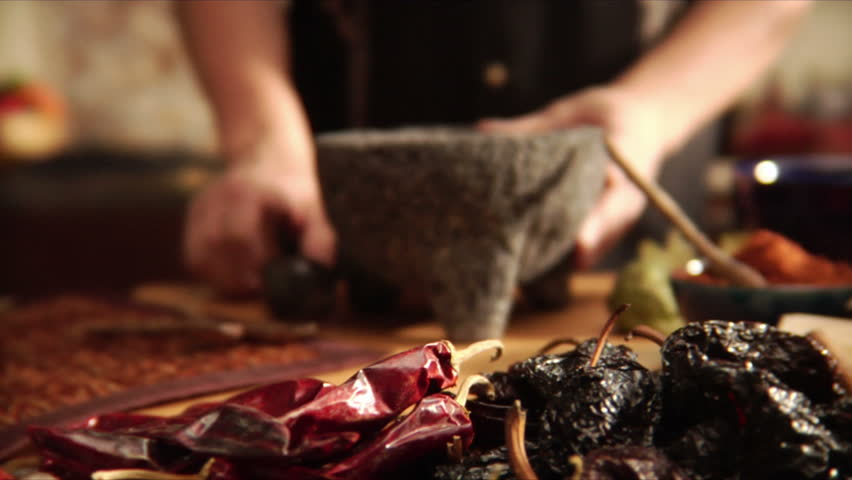 Chef crushing mexican spices with mortar and pestle
