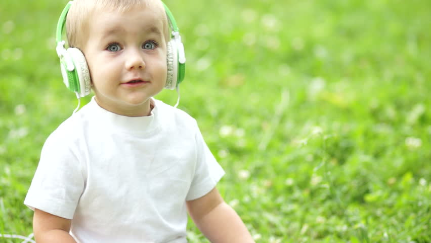 Cheerful child with a Tablet PC sitting on the grass