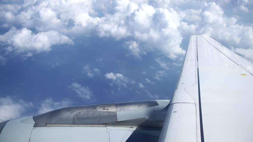 Wing of a airplane flying over clouds, 4K Aerial Video Footage #25493873