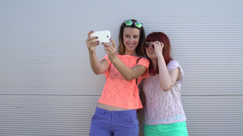 Two best friends girls having fun and making selfie. Two hipster girls taking selfie photos with smart phone. | Shutterstock HD Video #25567277
