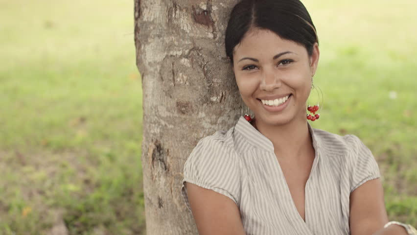Portrait of happy young latina woman smiling under tree in park. Tilt shot
