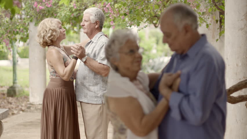 Active elderly people and recreation, group of happy senior men and women dancing latin american dance at party on vacation