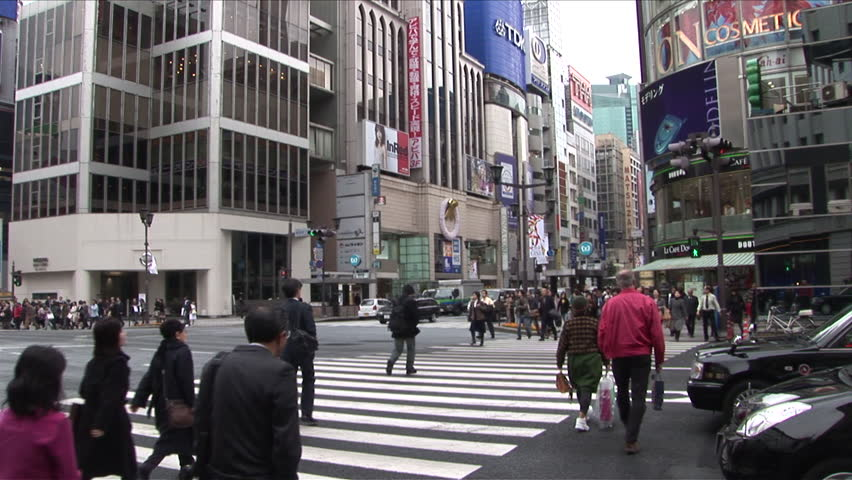 Tokyo, Japan - CIRCA November, 2006: Wide shot of many people crossing a busy intersection in a busy shopping area during the day - HD stock footage clip