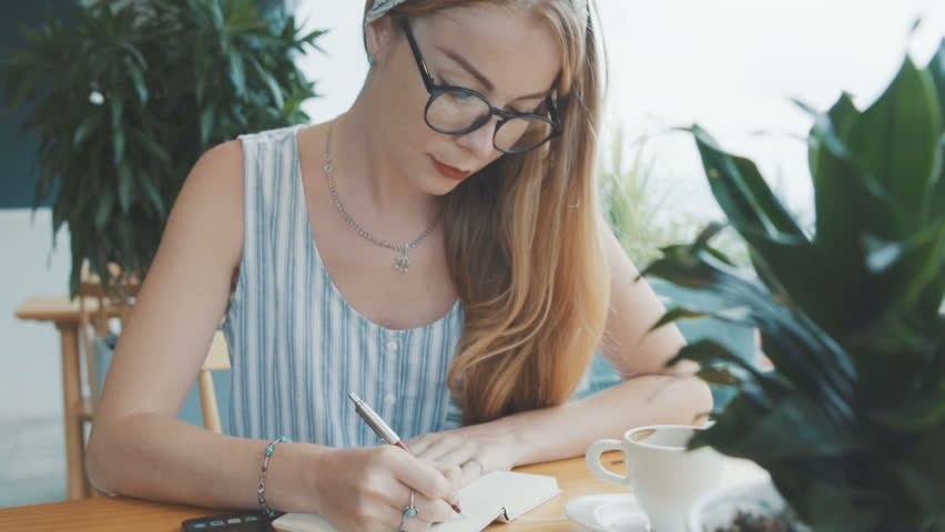 Pretty woman studying and writing in notebook. Female sitting at table in cosy cafe. | Shutterstock HD Video #25690370