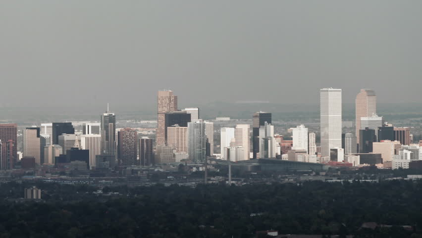 Sunlight shines on Denver, Colorado on a hazy winter day. HD 1080p aerial pan