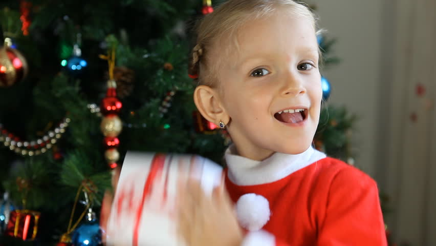 Child Shaking Her Gift Near Christmas Tree, Happy Little ...