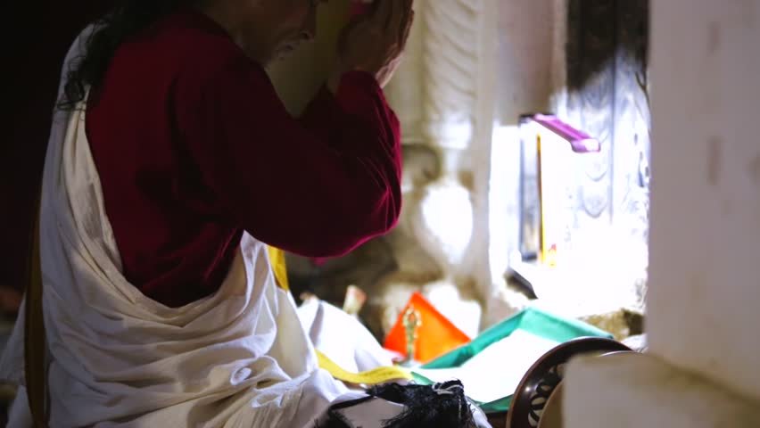 KATHMANDU, NEPAL - MAY 27, 2016: Old monk sings mantras and meditates near Boudhanath stupa, one of the largest and holiest in the world.   Shutterstock HD Video #25751876