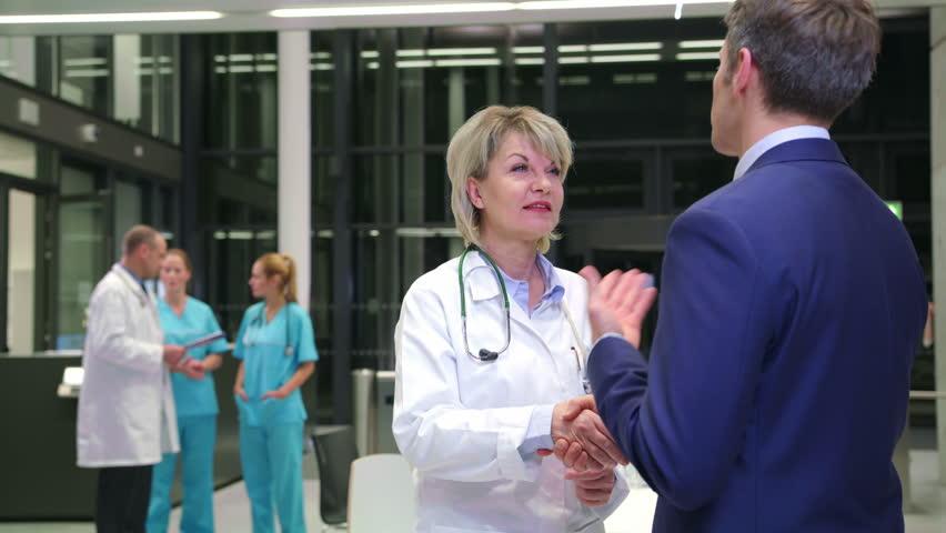 Female doctor shaking hands with businessman in corridor at hospital | Shutterstock HD Video #25810646