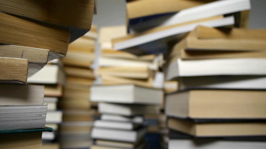 Camera tracks through teetering piles of books.