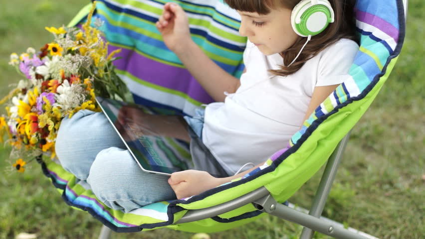 Girl in headphones listening  music from Tablet PC outdoors
