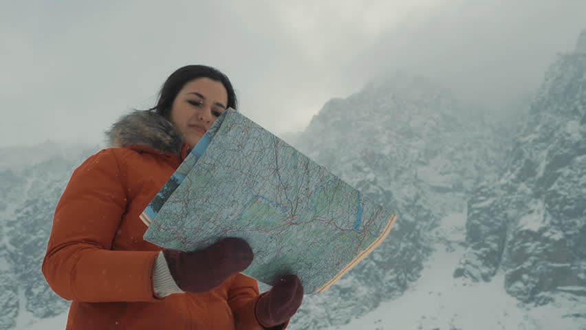 Girl is studying a map against the background of snow-capped mountains. Searches his way where to go. Search your way on the journey. Enjoys traveling or adventure. Mountain travel, Snow in mountains   Shutterstock HD Video #26033144