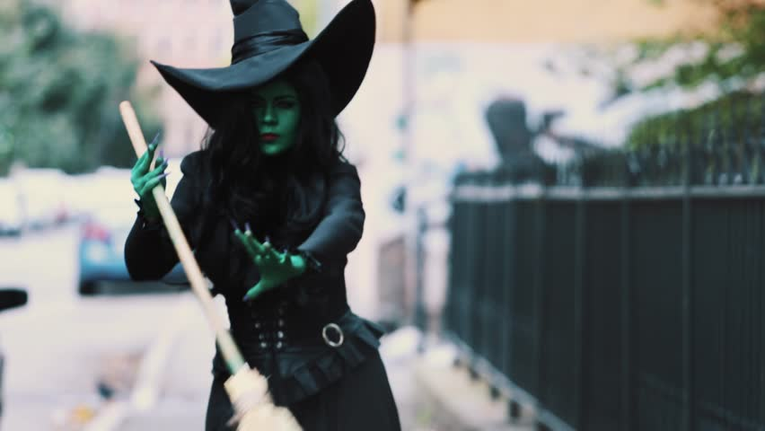 Cosplayer in halloween outfit of green witch from The Wizard of Oz walking down autumn city street holding broom, look into distance and accelerate | Shutterstock HD Video #26065481