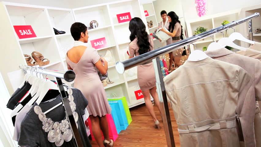 Young multi ethnic girlfriends shopping together in exclusive fashion boutique