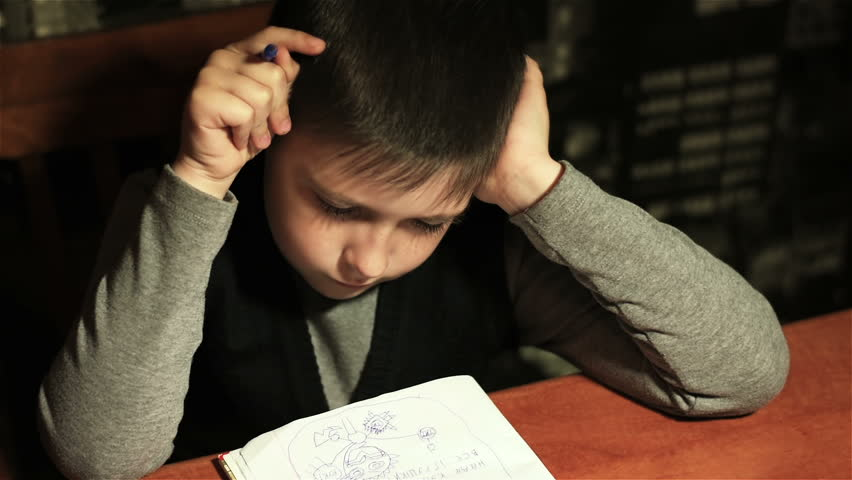 Tired schoolboy draws abstract animals in his notebook | Shutterstock HD Video #26129381