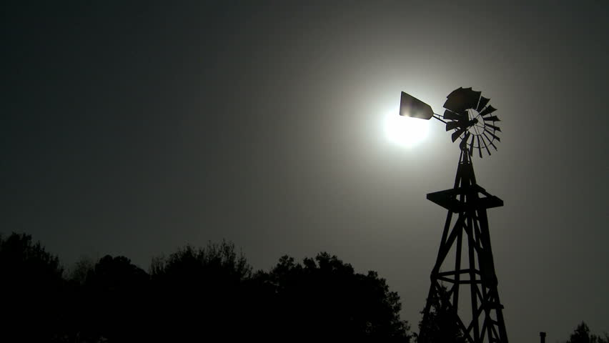 Vintage Windmill rotating in the wind with the sun shining in the background