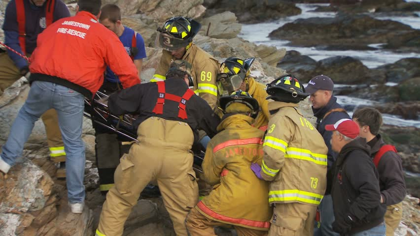 JAMESTOWN, RHODE ISLAND - CIRCA NOVEMBER 2010: Rescue crews carrying stretcher with woman on rocky shore - closeup